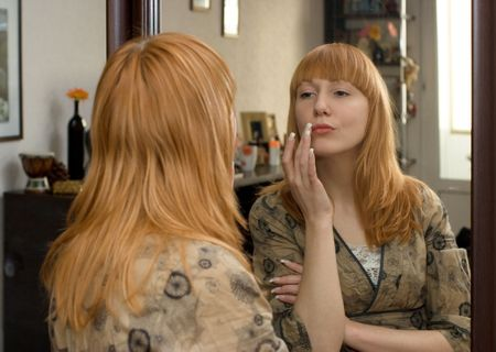 nice red-haired girl with well-groomed manicure finishes morning make-up at mirror Stock Photo