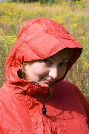 Young girl in red raincoat on background yellow flowers