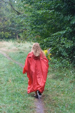 waterproof: Young girl in red raincoat with yellow flowers go out