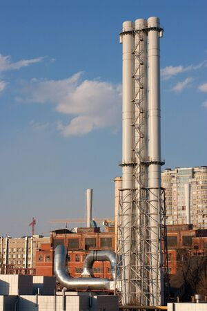 New chimney of old power station in center of Kyiv - the capital city of Ukraine - on blue sky and new build background Stock Photo