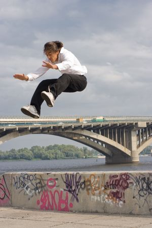Tracer jumping in Kyiv of capital city of Ukraine. On background river Dniepr and Metro bridge