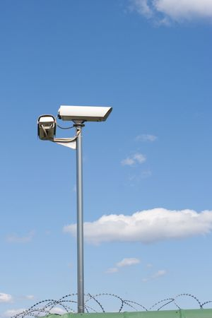 Surveillance camera on the wall with barbed wire on blue sky bacground