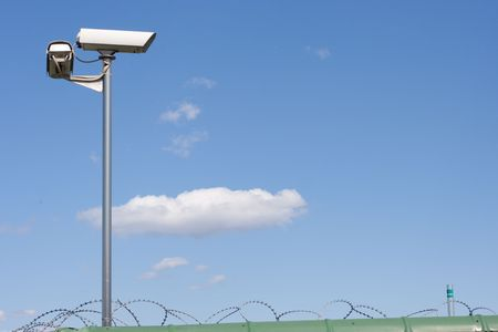 Surveillance camera on the wall with barbed wire on blue sky bacground photo