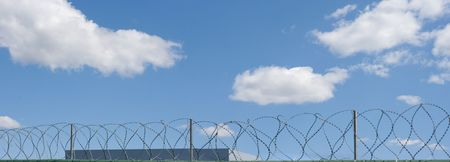 Barbed wire on the wall of plant on blue sky background