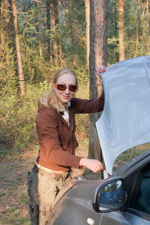 Pretty girl checking engine of her car after forest party