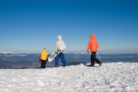 Skiers and snowboarder on the top of mountain in ukrainian Carpathian.  On background in the distance ukrainian Horgany (Dobushanka, Syniak, Khomiak) Stock Photo