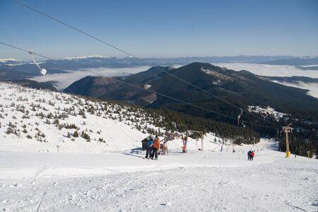 Young girl and guy on elevator at mountain Stig i ukrainian Carpathian. On background snowcaped mountains Doboshanka, Synyak, Khomyak (from left to right) Stock Photo