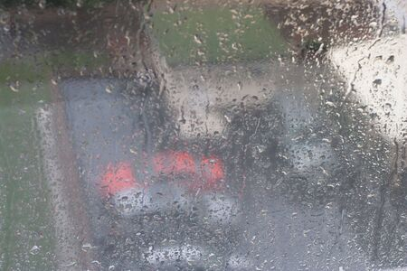 vague: View trough windon to rainy street. Focus on raindrop on glass Stock Photo