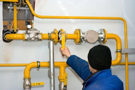metro de medir: Trabajador apertura de tornillo en la estaci�n de distribuci�n de gas Foto de archivo