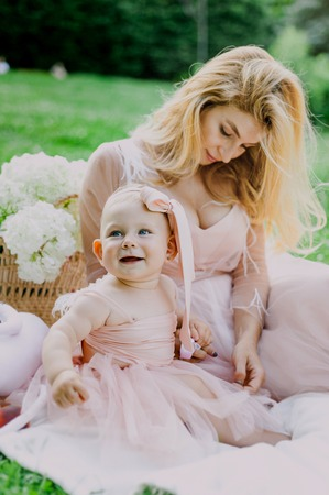 Woman in pink dress raises up her little daughter in the same clothes in park
