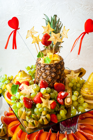 Fresh fruits and berries of different bright colors cut in small pieces are served on a table