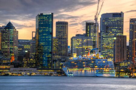 ocean cruise liner Carnival Legend parked in the Sydney Harbour near Circular Quay in New South Wales against the background of a skyscrapers Foto de archivo