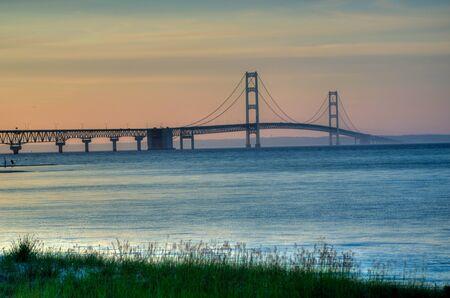 The Mackinac Bridge standing tall in Lake Michigan at sunset