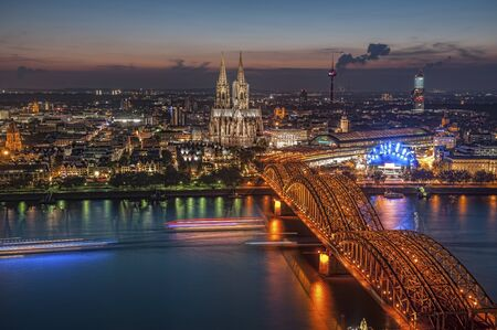 Koelner Dom Sankt Petrus (meaning St Peter Cathedral) gothic church and Hohenzollernbruecke (meaning Hohenzollern Bridge) crossing the river Rhein at night in Koeln, Germany