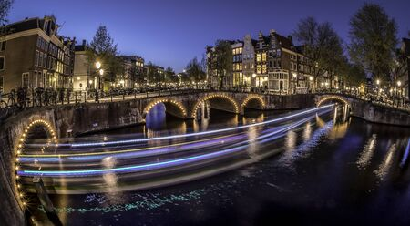 Amsterdam canal, bridge and typical houses, boats and bicycles during evening twilight blue hour, Holland, Netherlands. Used toning. Stock Photo