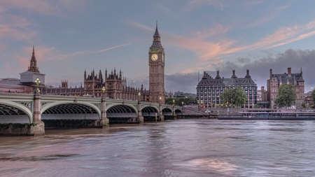 Houses of Parliament with Big Ben and double-decker buses on Westminster bridge at sunset, London, United Kingdom Editorial