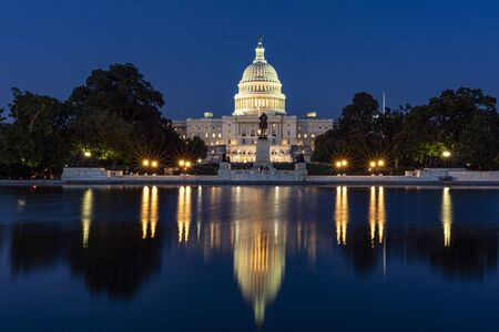 Capitol hill building at night illuminated with light with lake reflection Washington DC.