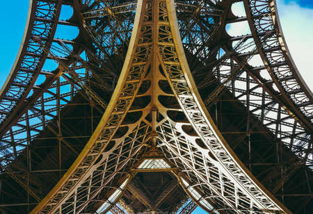 Inside the Eiffel Tower in Paris, France. View to the inside of Eiffel Tower. Big symetrical building. Close up shot in the morning. Blue sky with a sunny weather Banque d'images