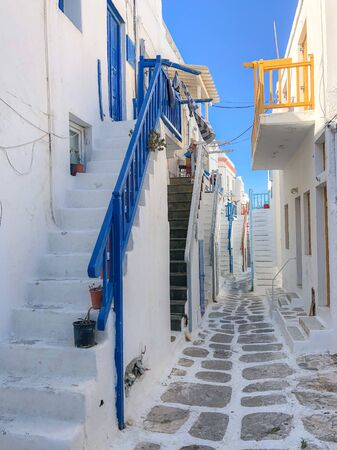 Perspective of old street with whitewashed houses in Mykonos island, Chora town, Greece