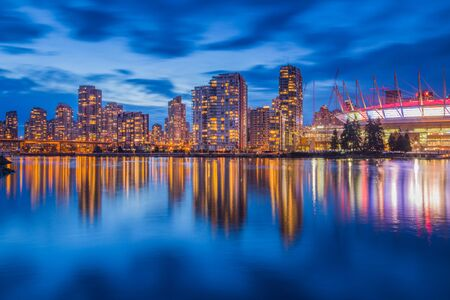 Vancouver downtown architecture and boat with water reflections at dusk