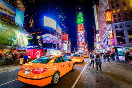 Times Square at night in busy main street with taxi cabs driving in New York, Manhattan, most famous tourist destination in the world.