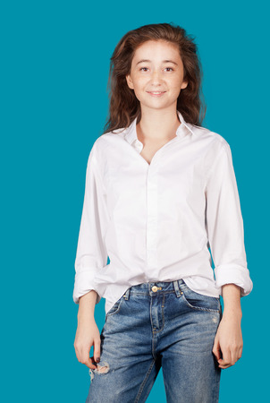 16 17: Young cheerful girl on a blue background, wearing jeans and a white shirt