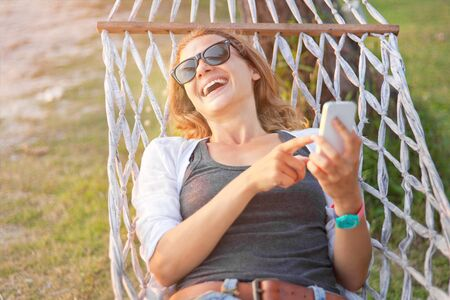 Happy beautiful young woman with a mobile phone in a hammock. Summer concept Stock Photo
