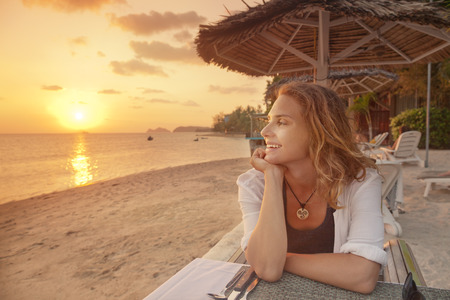 mujer mirando el horizonte: Hermosa mujer joven sentada en el caf� en la playa y ver el atardecer