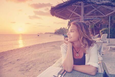 mujer mirando el horizonte: Hermosa mujer joven sentada en el café en la playa y ver el atardecer