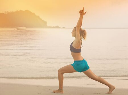 activity holiday: Young woman doing yoga on the beach at sunset. Sport, activity, holiday, healthy lifestyle. Stock Photo