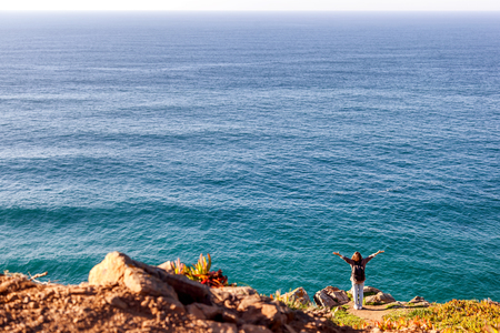 young woman on the background of the Atlantic Ocean, at Cape Cabo da Roca, Portualia. A huge ocean and a little human