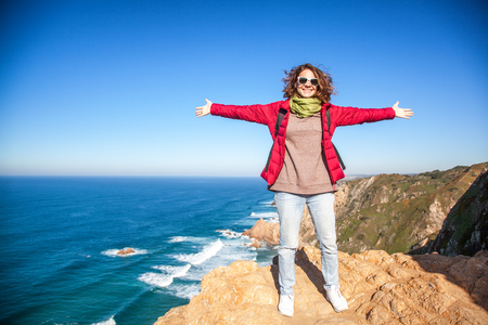 a young beautiful woman spread her arms and embraces the whole world, against the backdrop of Cape Cabo da Roca, Portugal, the Atlantic Coast. Freedom, youth, travel