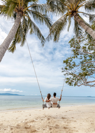 Young couple swinging on a swing on paradise tropical beach, honeymoon, vacation, travel concept Reklamní fotografie - 117351273