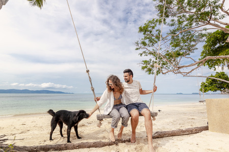 Young couple swinging on a swing on paradise tropical beach with dog, honeymoon, vacation, travel concept Banco de Imagens - 117351394