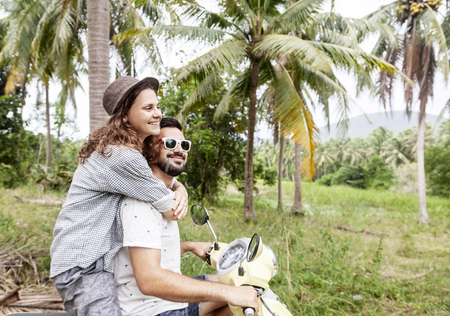 Happy multinational couple traveling on a motorbike in the jungle, honeymoon, vacation,