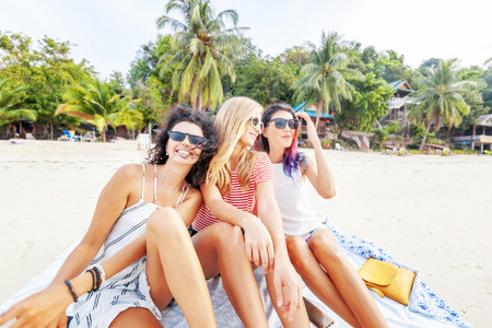 Three young beautiful girlfriends relax and have fun on a tropical beach, travel and vacation concept