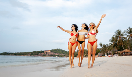 Three beautiful slender happy girlfriends walk along the sandy beach having fun on the background of the sea, vacation time and travel