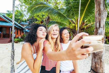 Three beautiful slender happy girlfriends students take selfie against the backdrop of a tropical resort, vacation and travel vacations in hot countries Stockfoto