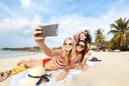 Beautiful happy girlfriends having fun on the beach taking selfies during vacation and travel, laying on the sand