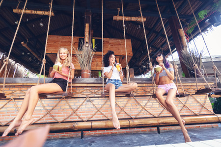 Three young beautiful slender girlfriends drink necks and coconuts in a stylish beach bar, at bar counter Stockfoto