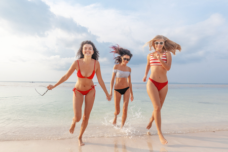 Three beautiful slender happy girlfriends having fun on the beach rejoicing and having fun against the background of the sea, vacation time and travel Stockfoto