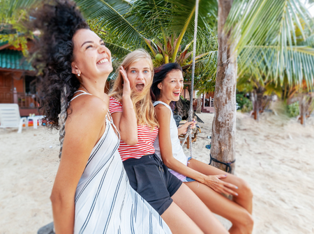 Three beautiful slender happy girlfriends students swing on a swing against the backdrop of a tropical resort, vacation and travel vacations in hot countries Stockfoto