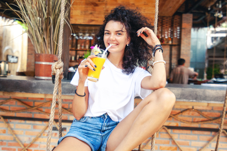 Beautiful young slim woman with dark curly hair, in denim shorts with long tanned legs, drinks fresh orange mango in a stylish beach bar Stockfoto