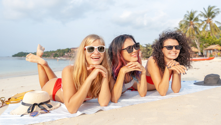 Three young beautiful girlfriends in bikini relaxing on a tropical beach, travel and vacation concept Stockfoto
