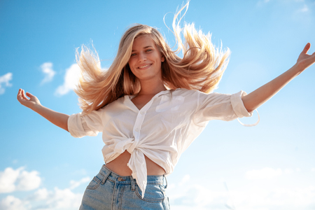 Beautiful young blonde girl with flowing hair and dimples against the blue sky and the sun, beauty and fashion Stok Fotoğraf