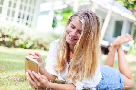 Beautiful blonde girl, on a summer green lawn, with a smartphone in her hands enjoys the sun of summer and spring Stockfoto