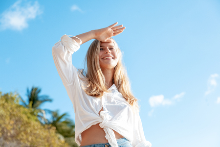 Beautiful young blonde girl with flowing hair and dimples against the blue sky and the sun, pretty smile with dimples,