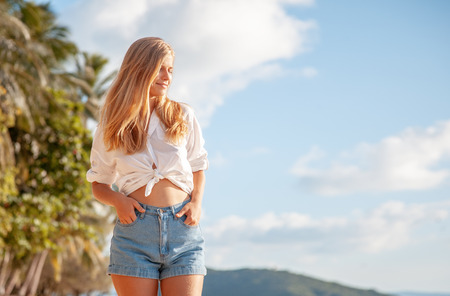 Beautiful young blonde girl with flowing hair and dimples against the blue sky and the sun