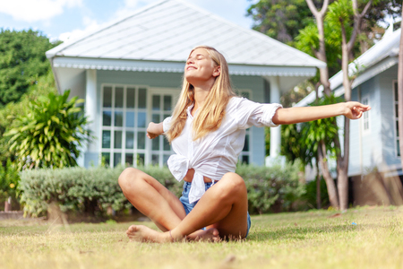 Beautiful young blonde woman at summer green lawn, enjoys the sun spring and summer. Beautiful woman face. Relax concept.