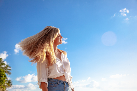 Beautiful young blonde girl with flowing hair and dimples against the blue sky and the sun, beauty and fashion Stockfoto